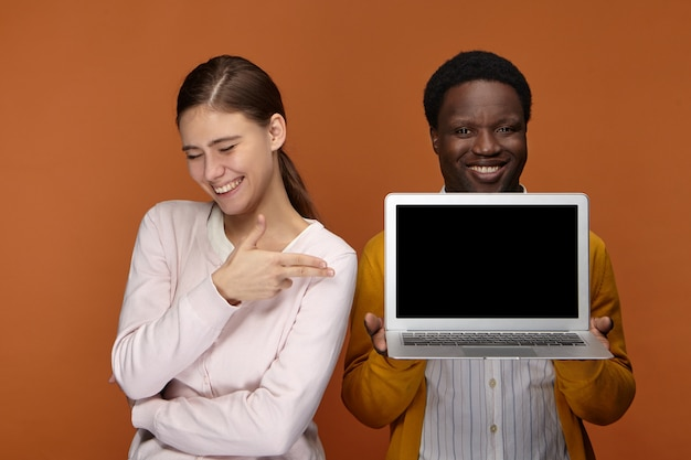 Twee getalenteerde jonge professionals die genieten van het samenwerken in team: vrolijke zelfverzekerde zwarte man met generieke laptop terwijl positieve schattige witte vrouw wijzend op leeg scherm, presentatie tonen