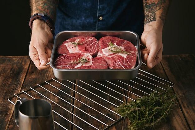 Twee getatoeëerde handen bieden een stuk geweldige vleesbiefstuk aan in een zilveren stalen pan met kruiden met bot voor de camera