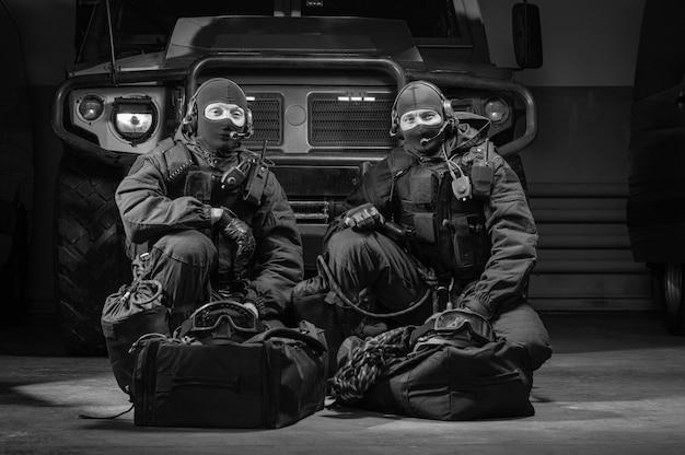 Twee geüniformeerde commando's zitten in een hangar met een militaire vrachtwagen op de achtergrond. swat-concept. gemengde media