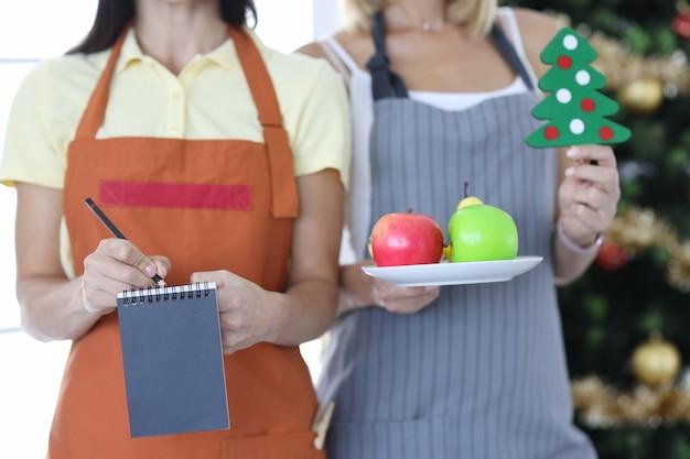 Twee geüniformeerde obers houden een bestelblok en een bord fruit vast tegen de achtergrond van een kerstboom