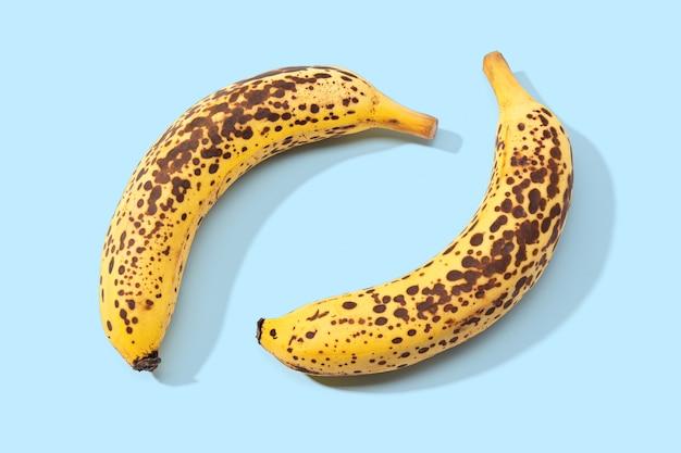 Twee gevlekte banaan geïsoleerd op blauwe achtergrond