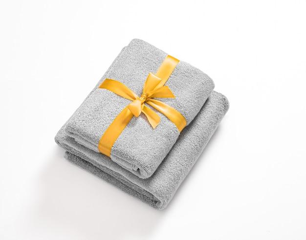 Twee gevouwen badstofhanddoeken die door oranje geïsoleerd lint worden gebonden. stapel grijze badstofhanddoeken tegen een witte achtergrond.