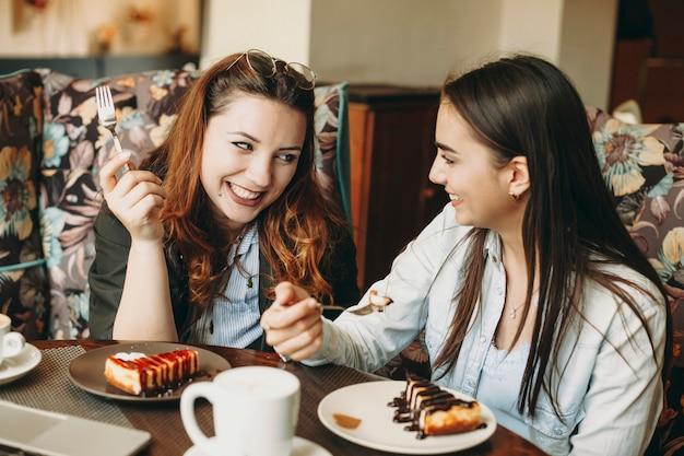 Twee geweldige blanke vrouw zitten in een coffeeshop lachend met plezier tijdens het eten van een cake en koffie drinken.