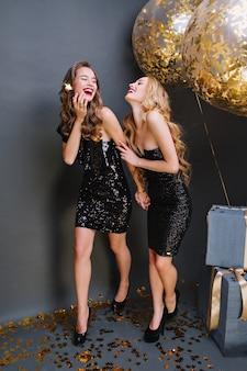 Twee geweldige grappige jonge vrouwen in luxe zwarte jurken feest vieren. lang krullend haar, aantrekkelijk uiterlijk, rode lippen, opgewekte stemming, lachen, plezier maken, gelukkig verjaardagsfeestje.