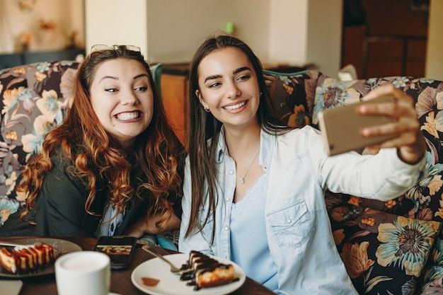 Twee geweldige jonge vrienden doen een grappige selfie terwijl ze in een coffeeshop zitten met plezier samen.
