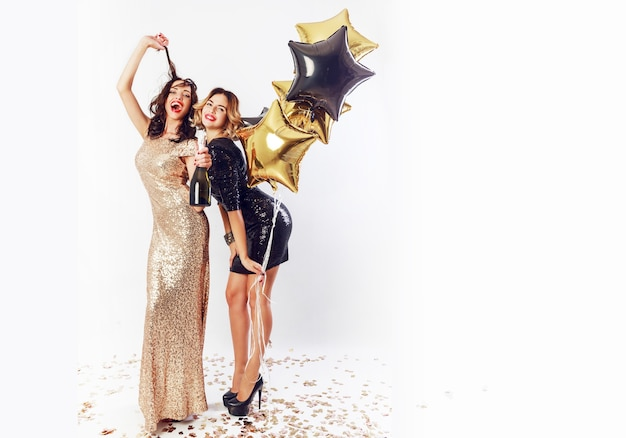 Twee geweldige sexy vieren vrouw met rode lippen, lachen, poseren. een fles champagne vasthouden, plezier maken. volledige lengte.