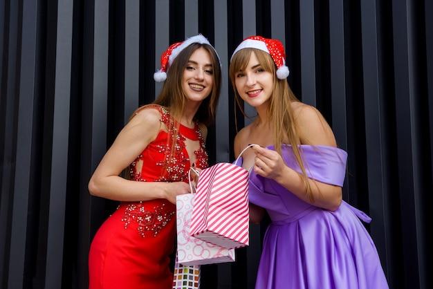 Twee geweldige vrouwen in kerstmutsen en elegante avondjurken met boodschappentassen