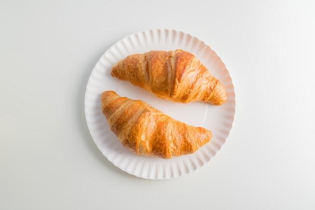 Twee gewone croissants op de plaat, witte tafel achtergrond.