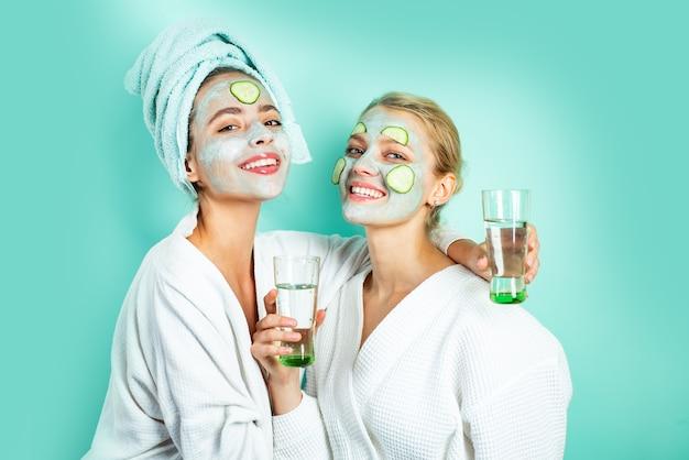 Twee gezonde natuurlijke meisjes glimlachen en drinken water, vochtinbrengend klei-moddermasker en plakjes komkommer bij...