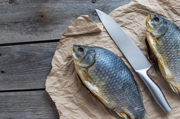 Twee gezouten droge vissen vobla met een scherp mes op verfrommeld kraftpapier op houten, heerlijke biersnack