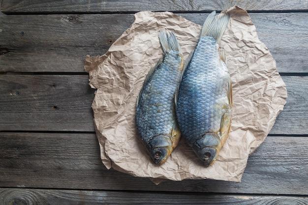 Twee gezouten droge vissen vobla op verfrommeld kraftpapier op houten, heerlijke biersnack bovenaanzicht
