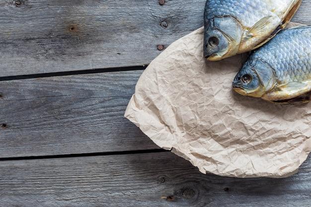 Twee gezouten droge vissenvobla op verfrommeld kraftpapier op houten