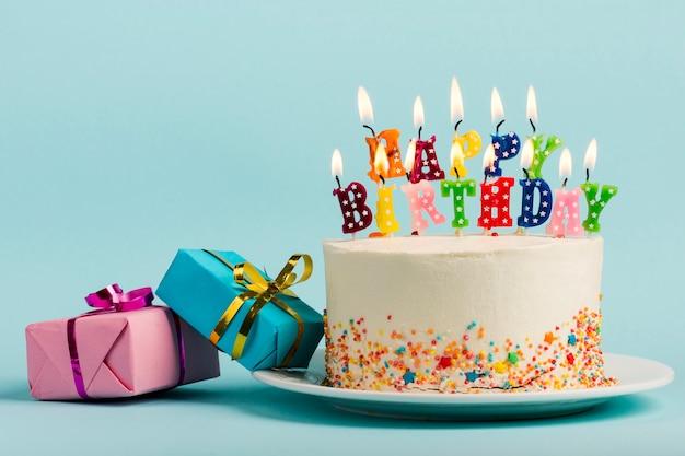 Twee giftdozen dichtbij de cake met gelukkige verjaardagskaarsen tegen blauwe achtergrond