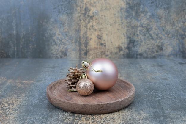 Twee glanzende kerstballen met een dennenappel op houten plaat