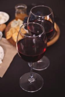 Twee glas rode wijn en bord met diverse kaas, fruit en andere snacks voor feest
