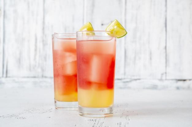 Twee glazen bay breeze-cocktail gegarneerd met limoenwiggen op houten achtergrond