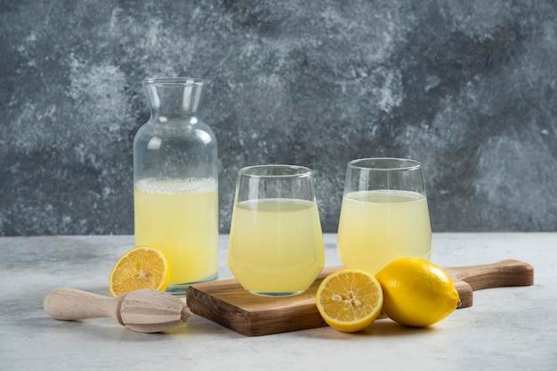 Twee glazen bekers citroensap en pot op een houten bord.
