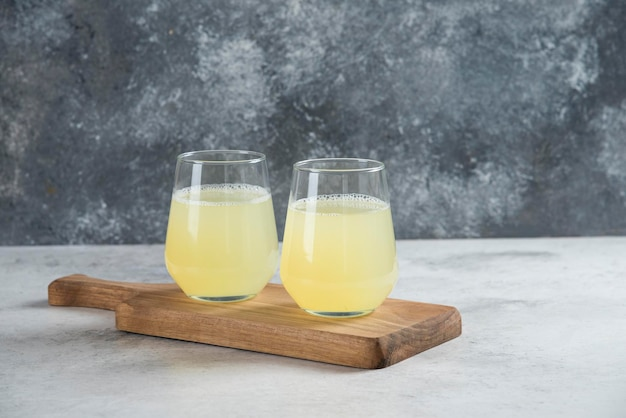 Twee glazen bekers citroensap op een houten bord.