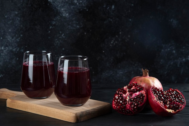 Twee glazen bekers granaatappelsap op donker.