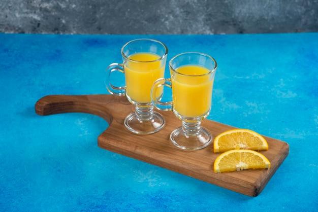 Twee glazen bekers lekker jus d'orange op een houten bord.