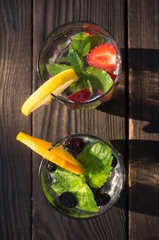 Twee glazen bekers met drank van munt en bessen op de donkere achtergrond van de planken