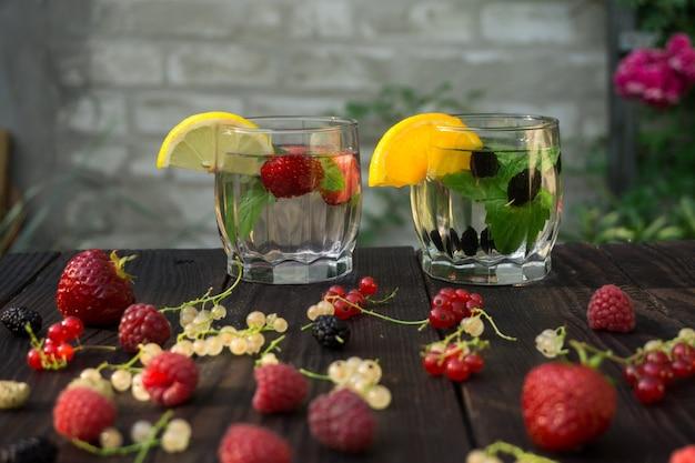 Twee glazen bekers met drank van munt en bessen staan op de donkere planken op bakstenen muurachtergrond