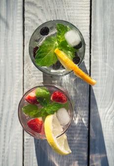 Twee glazen bekers met drankje van munt en bessen op een wit bord