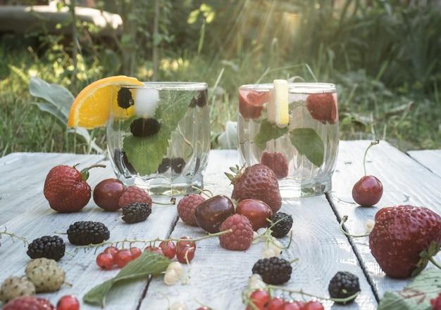 Twee glazen bekers met een drankje van munt en bessen op een wit bord op een tuinachtergrond
