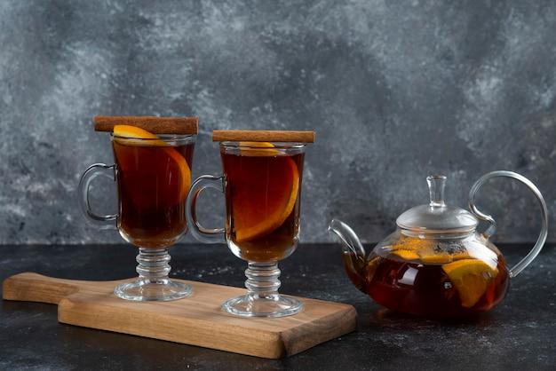 Twee glazen bekers met heerlijke thee en kaneelstokjes.