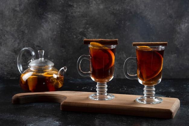 Twee glazen bekers met hete thee en kaneelstokjes.