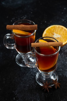 Twee glazen bekers met lekkere thee en kaneelstokjes.