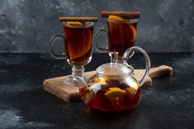 Twee glazen bekers met thee en kaneelstokjes.