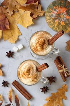 Twee glazen bekers pompoen latte met kruiden op grijze achtergrond met pompoenen en herfstbladeren