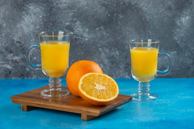 Twee glazen bekers sinaasappelsap op een houten bord.