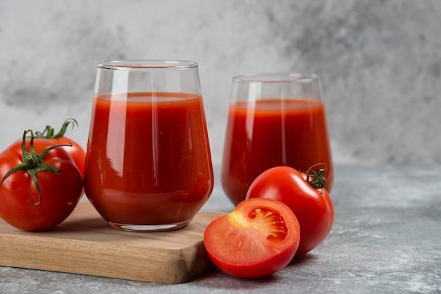 Twee glazen bekers tomatensap op een houten bord.