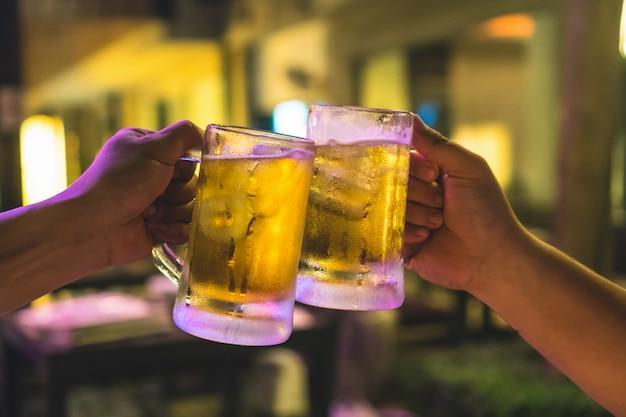 Twee glazen bier proosten samen tussen vrienden in de bar en het restaurant met weinig licht