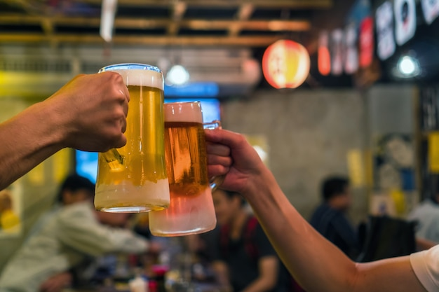 Twee glazen bier proosten samen tussen vrienden in de bar en in het restaurant