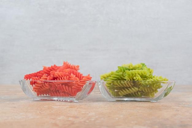 Twee glazen borden vol kleurrijke spiraalpasta op marmeren ruimte.