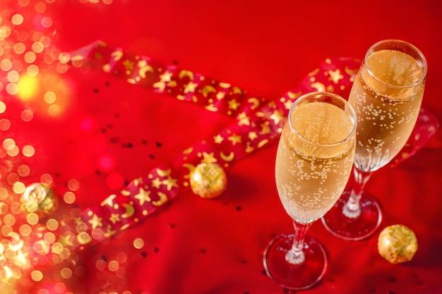 Twee glazen champagne en chocolade in een gouden wikkel op een rood fluweel