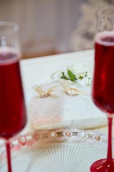 Twee glazen champagne en een kussen met trouwringen