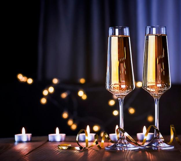 Twee glazen champagne en kaarsen op tafel