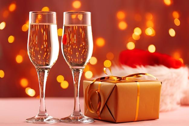 Twee glazen champagne en kerstmuts tegen bokeh lichten
