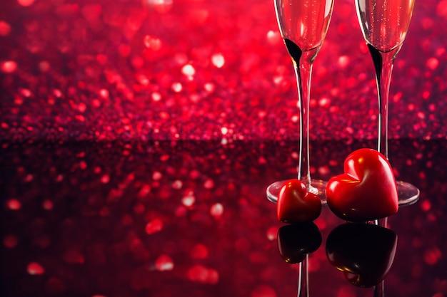 Twee glazen champagne en twee rode harten met rode hartvorm bokeh op achtergrond. romantisch diner. gelukkig valentijnsdag concept.