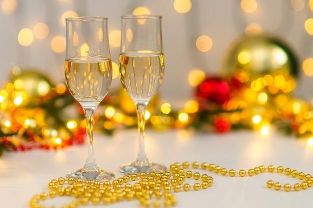Twee glazen champagne in geel en goud kerstdecor