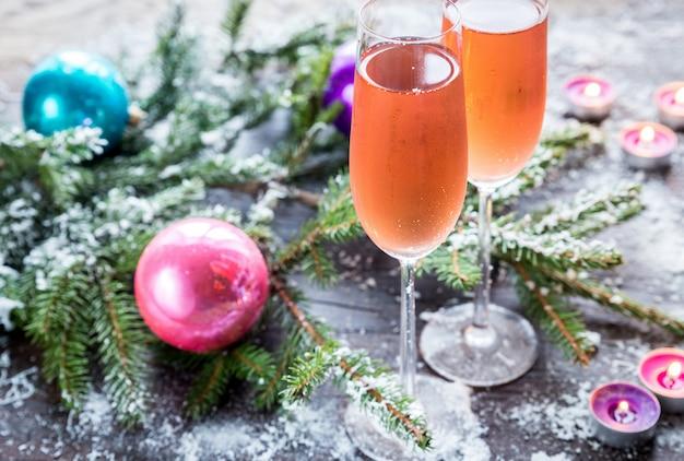 Twee glazen champagne met kerstboomtak
