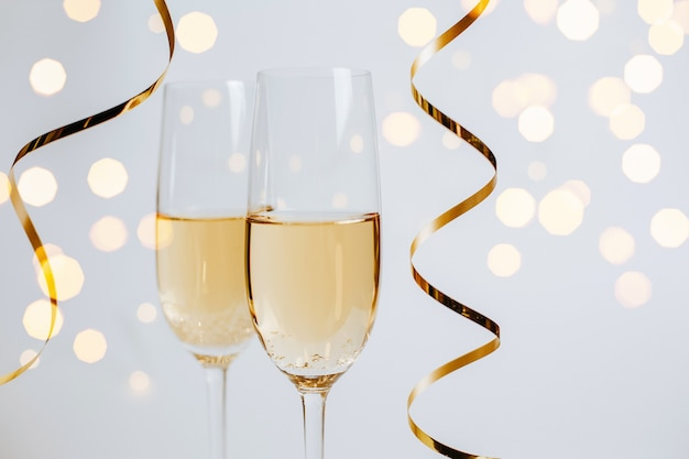 Twee glazen champagne met lichten en linten op een witte vakantie als achtergrond