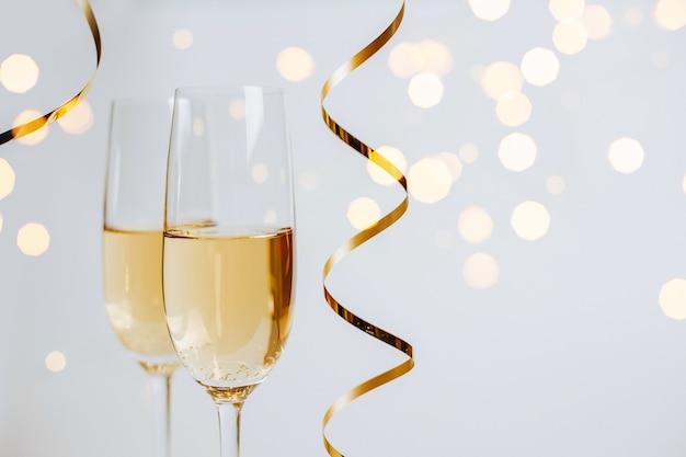 Twee glazen champagne met lichtjes en linten
