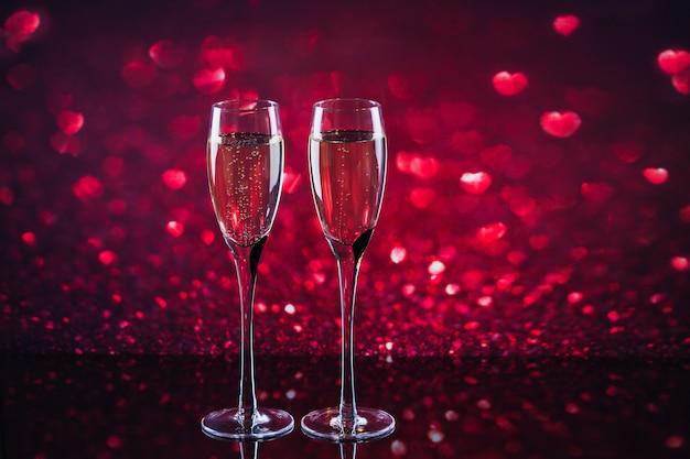 Twee glazen champagne met rode hartvorm bokeh op achtergrond. romantisch diner. gelukkig valentijnsdag concept.