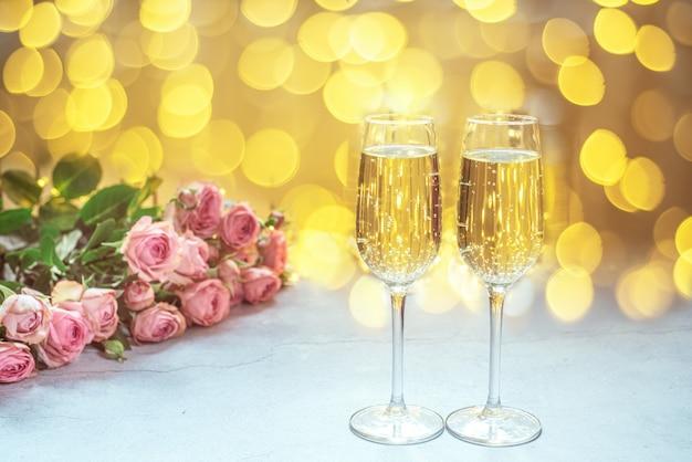 Twee glazen champagne met roze rozenboeket