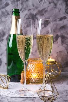 Twee glazen champagne naast een fles
